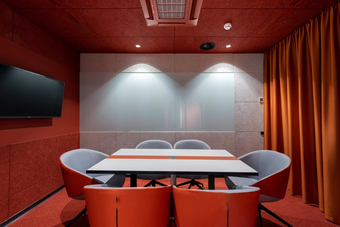 Comfortable red chairs placed around white table in modern conference room with TV and curtains in contemporary office of business center