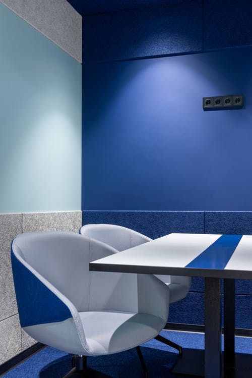 Comfortable armchairs at white table placed near blue wall in modern small workspace with stylish design in contemporary business center