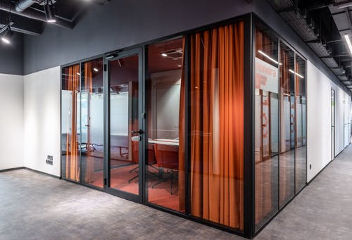 Hall of spacious contemporary business center with glass walls of modern office with colorful armchairs at table and red curtain