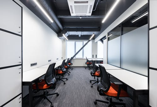 White desks with comfortable colorful chairs placed in spacious workspace with window and glass partitions in contemporary financial business center
