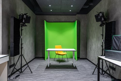 Table with armchair near green background in studio
