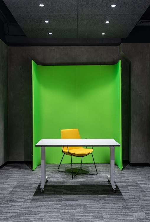 Comfortable yellow chair at white table placed on floor in modern spacious professional studio with green wall and special supply