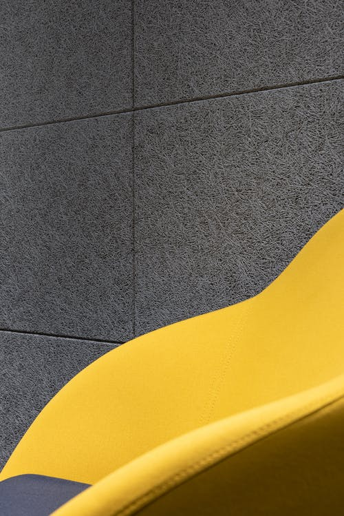 Detail of comfortable bright chair with yellow fabric and cushion placed near gray textured wall in room of modern studio