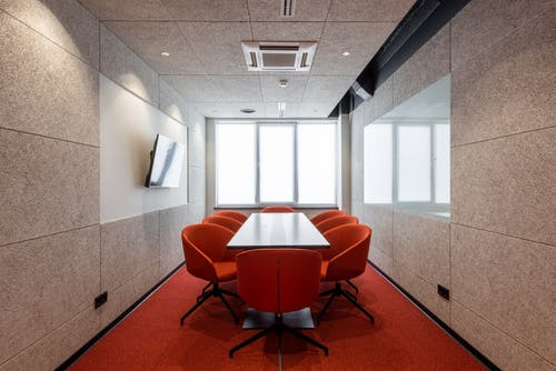 Orange chairs placed around white table in modern conference room with window and TV on wall in contemporary business center