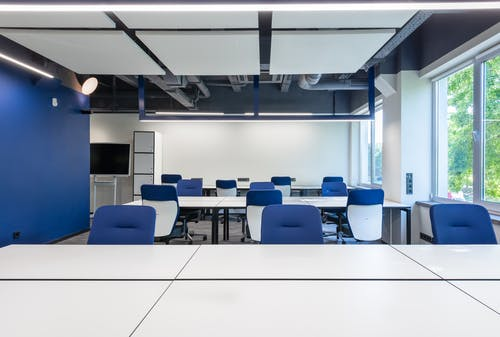 Various white desks with blue chairs placed in modern spacious workspace with big window and monitor in contemporary business center