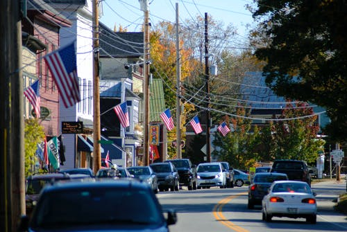 Busy road running through suburban district houses with USA flags