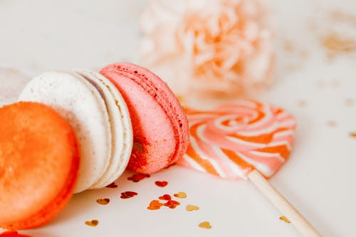 Macarons and Lollipop on White Surface