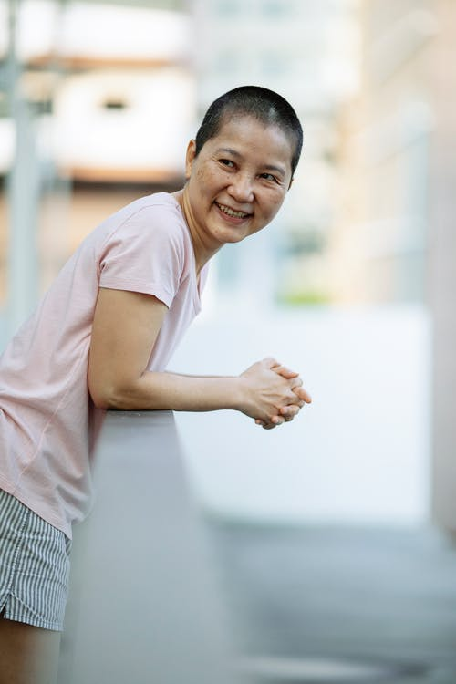 Cheerful short haired Asian woman with breast cancer smiling