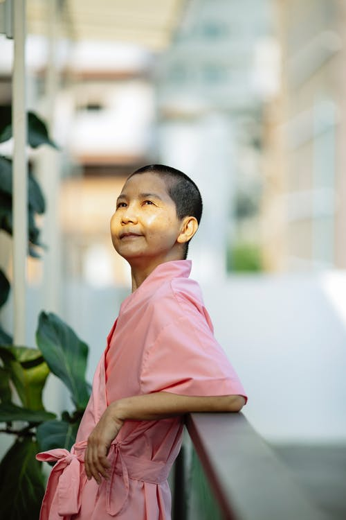 Happy Asian woman suffering from cancer on balcony