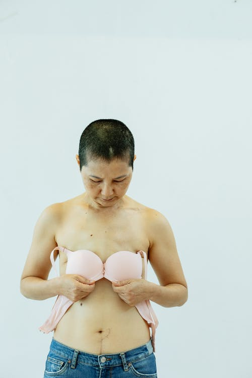 Serious mature female putting pink bra to chest after breast removal surgery from cancer while standing on white background in bright studio