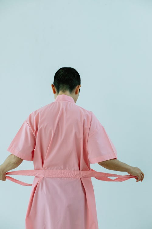 Back view of unrecognizable woman in pink bathrobe with belt standing on white background in light studio