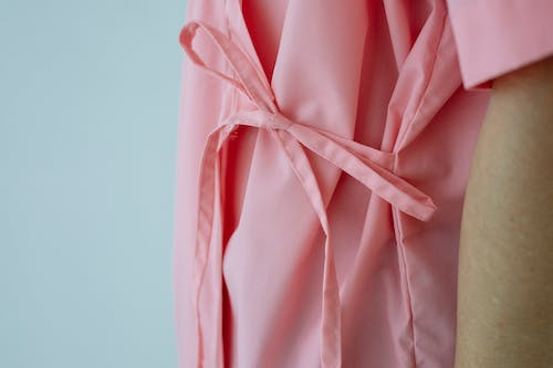 Crop unrecognizable female patient in pink gown with pink ribbon standing against white background