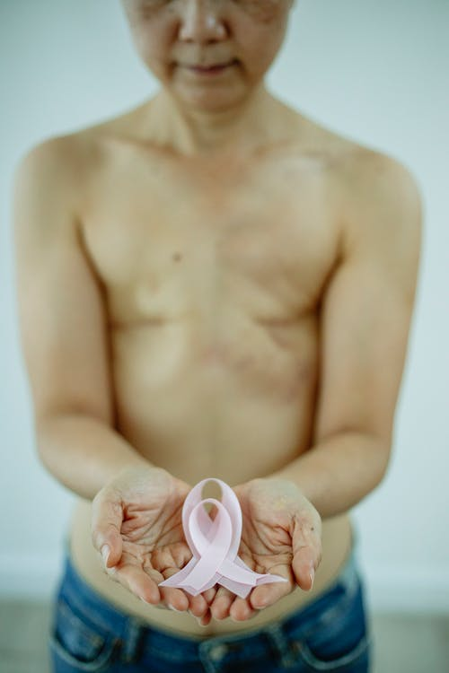 Crop unrecognizable woman with bare torso and scars left after operation holding pink ribbon in support to women with breast cancer on Breast Cancer day