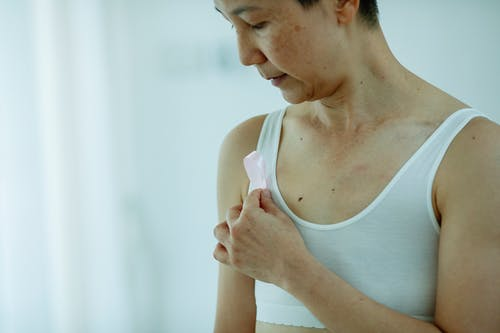 Crop adult female with short haircut pinning pink ribbon to white bra while standing on blurred background of light room
