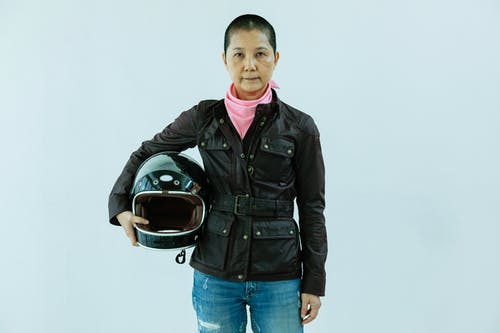 Adult Asian female biker with short hair wearing black leather jacket jeans and pink scarf holding helmet and looking at camera while standing on white background