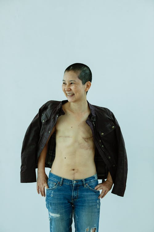 Smiling mature ethnic female in jeans and jacket with scars on chest after breast removal surgery from breast cancer standing in light studio on white background and looking away