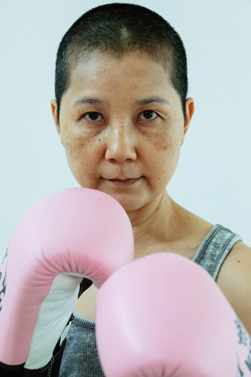 Calm Asian woman with short dark hair in pink boxing gloves looking at camera against gray background in studio