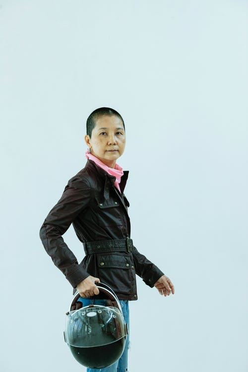 Senior Asian woman standing with motorcycle helmet and looking at camera
