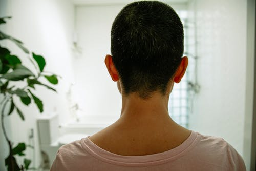 Faceless woman in bathroom near toilet and shower with bathtub
