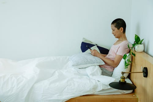 Ethnic woman using smartphone while sitting in bed