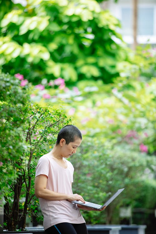 Asian woman with short hair using touchpad of laptop