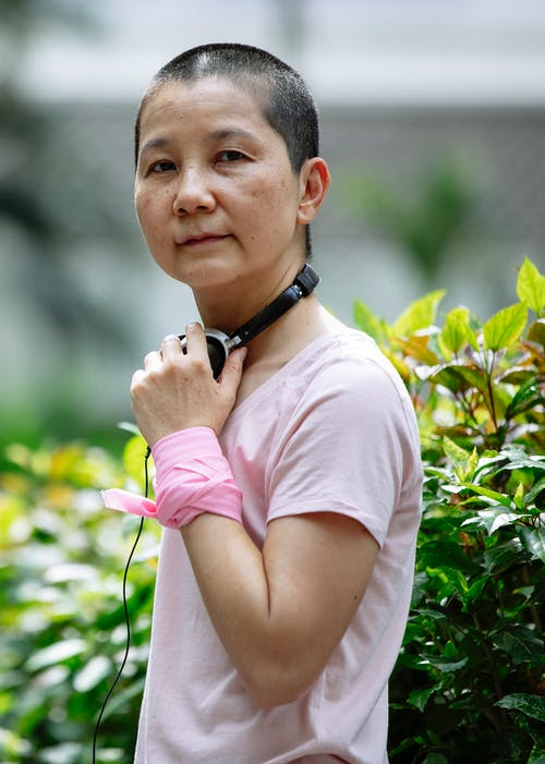 Sick Asian woman with short hair and tissue on hand