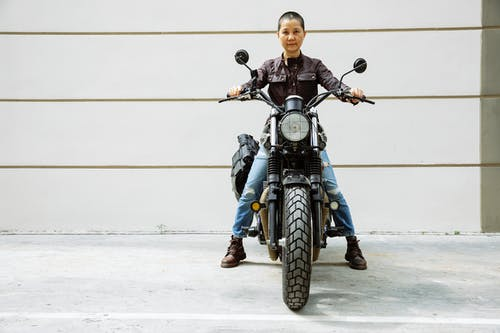 Serious mature Asian female biker in jacket and jeans sitting on black motorcycle on asphalt road in street near wall and looking at camera in daytime