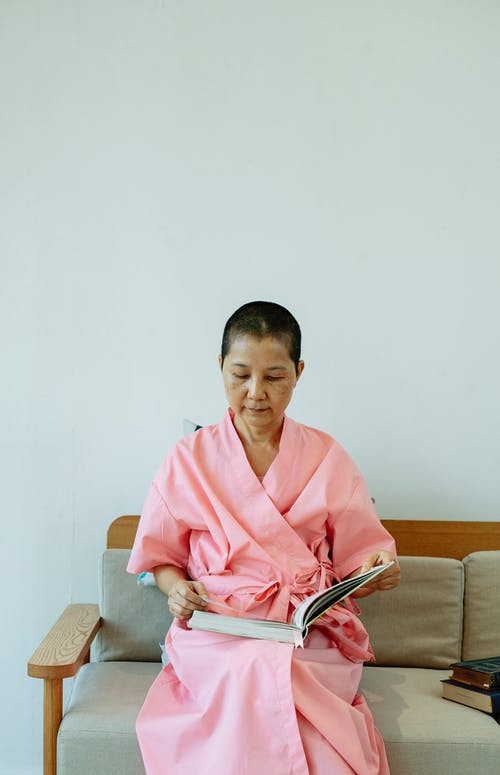 Pondering ethnic female with book in pink robe suffering from cancer resting on sofa in hospital