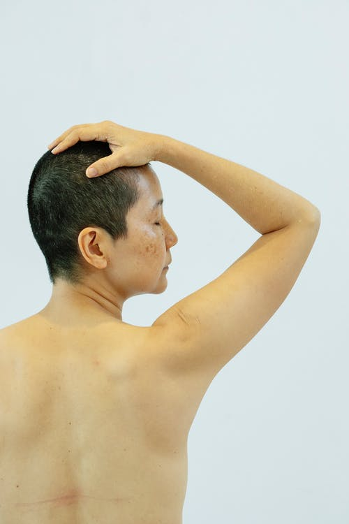 Back view of ethnic shirtless female with eyes closed on white background of studio