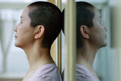 Side view of ethnic ill female with short dark hair leaning on mirror at home