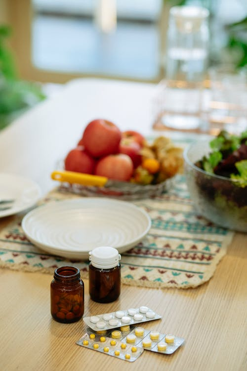 From above of fresh apples in plate composed with jars of pills on table