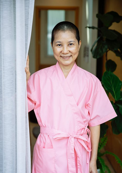 Positive Asian woman in pink robe suffering from breast cancer