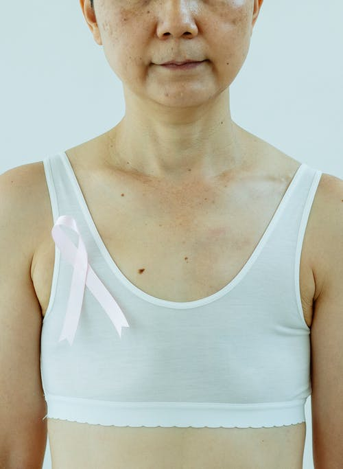 Woman in white top with pink ribbon as sign for Breast Cancer Day