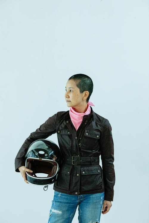 Asian woman standing with helmet and looking away against light background