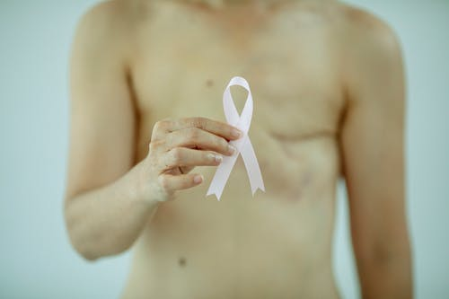 Crop anonymous female with breast cancer showing ribbon on white background of studio