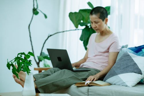 Full body of focused adult ethnic female freelancer with dark short hair in casual clothes working remotely on laptop while sitting on sofa at home