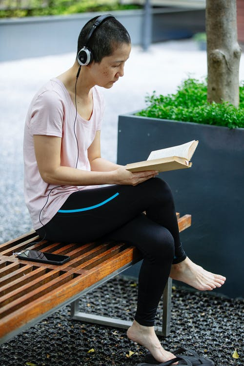 Side view of calm adult Asian female in casual clothes listening to music in headphones and reading interesting book while resting on wooden bench in city park on sunny day
