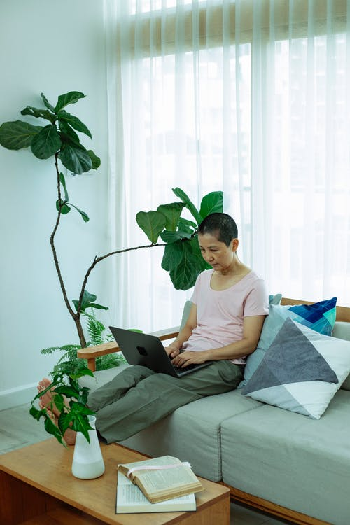 Serious ethnic self employed woman with dark short hair in casual clothes sitting on comfortable sofa and typing on laptop keyboard during remote work at home