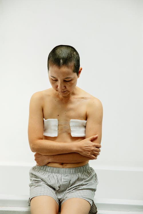Sad middle aged topless Asian female with short hair and gauze bandage on amputated breasts sitting on bathtub edge with crossed arms and looking down thoughtfully