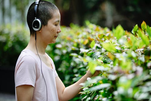 Asian woman listening to music in headphones in park