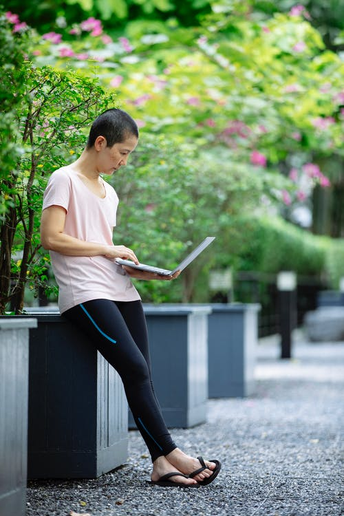Full body of concentrated Asian female freelancer in casual clothes leaning on wooden flowerpot in lush green garden and working remotely on laptop