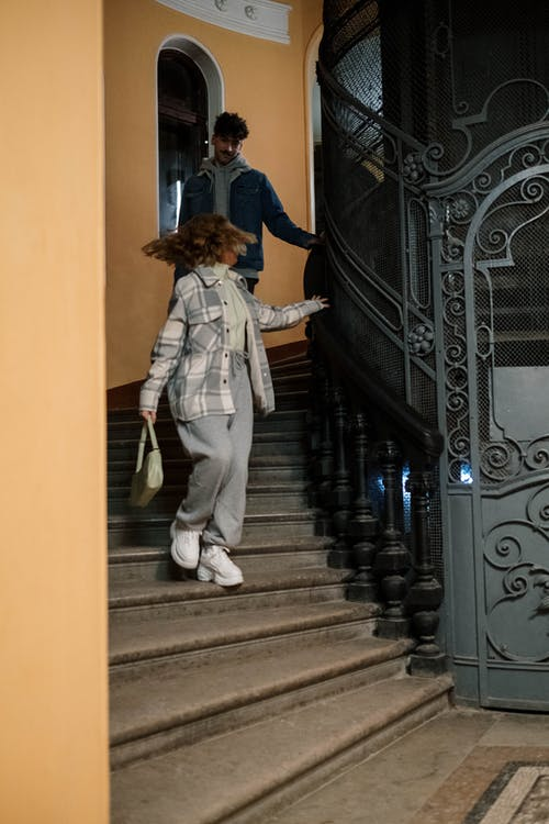 Woman in Gray Coat Walking on Staircase
