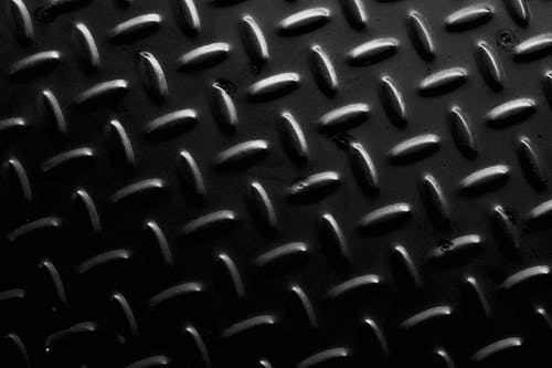 Textured background of metal floor with symmetrical oval bulges