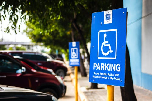 Signboard representing rule for disabled people parking only near vehicles and sidewalk in city