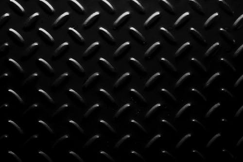 Full frame background of seamless geometric abstraction made of oval shaped bulges on black surface