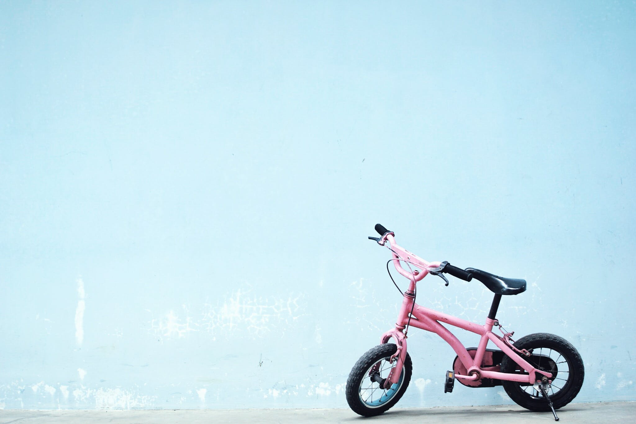 Toddler's Pink Bike Near Wall