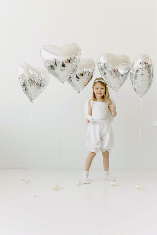 Girl in White Dress Holding White Balloons