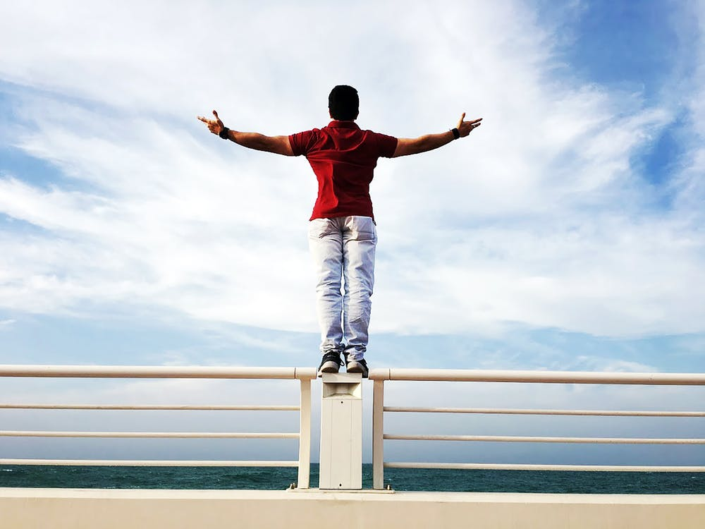 Person Raising Hands Mid-air Sidewards While Standing on Gray Steel Railings