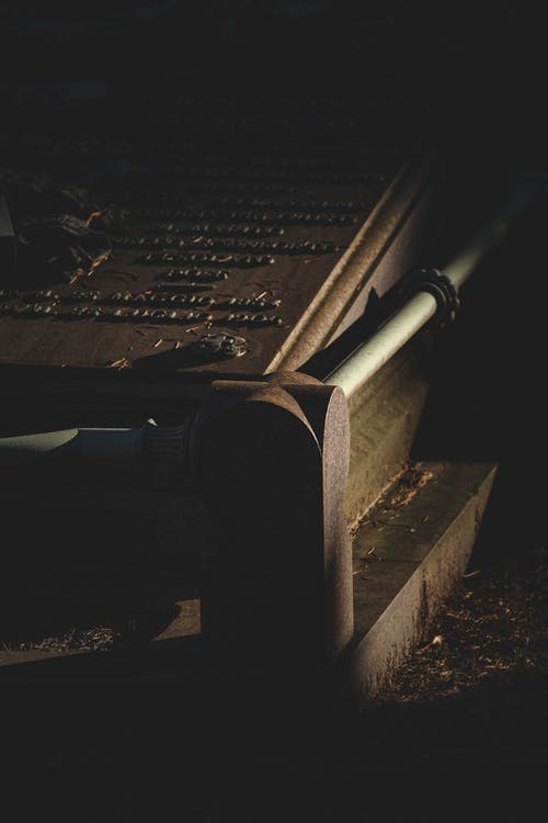Old stone tombstone in cemetery at night