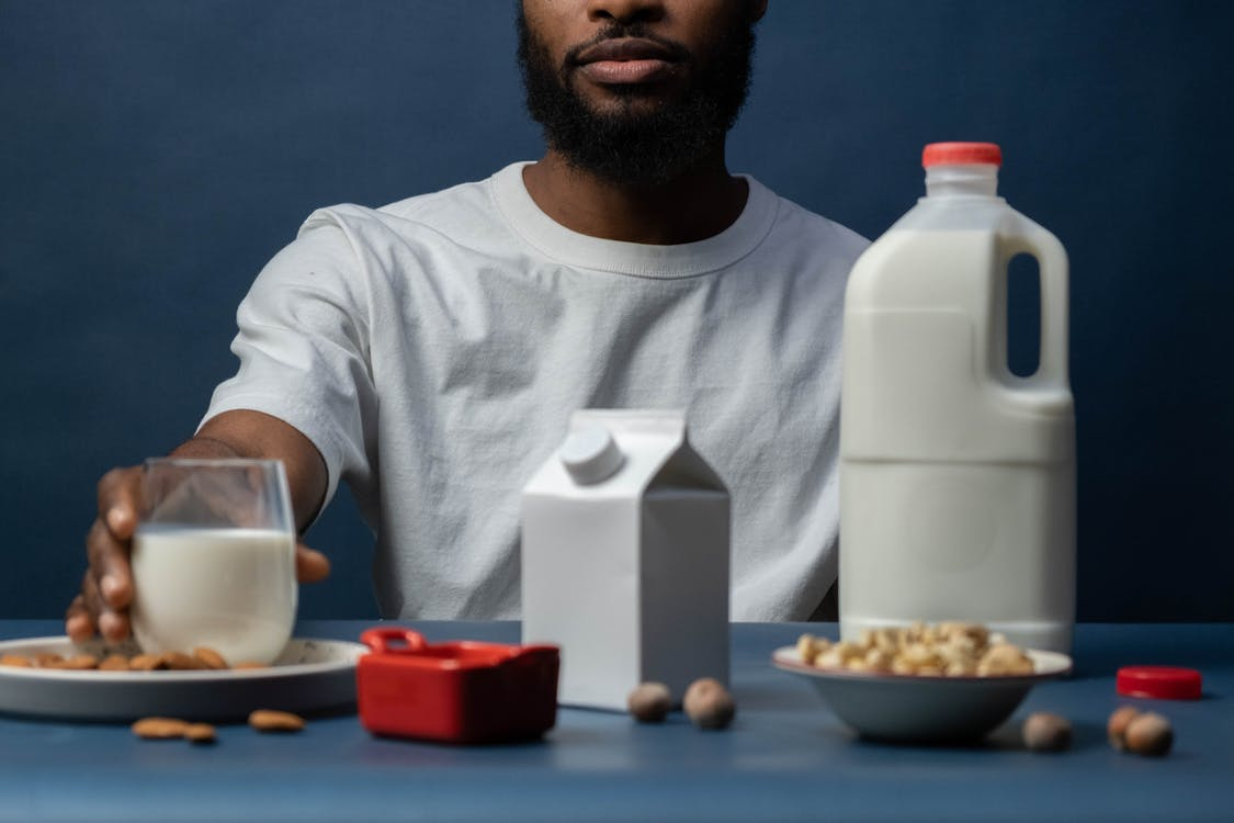 Man in White Crew Neck T-shirt Sitting Beside Table With Food
